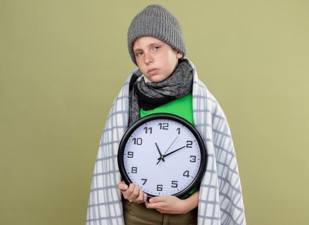 Ragazzino malato che indossa la maglietta verde in una sciarpa calda e cappello avvolto in una coperta che tiene l'orologio da parete sensazione di malessere malato e infelice in piedi sopra la parete chiara
