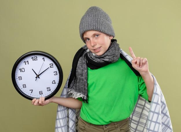 Ragazzino malato che indossa la maglietta verde in una sciarpa calda e cappello avvolto in una coperta che tiene l'orologio da parete sorridente che mostra il dito indice che si sente meglio in piedi sopra la parete chiara