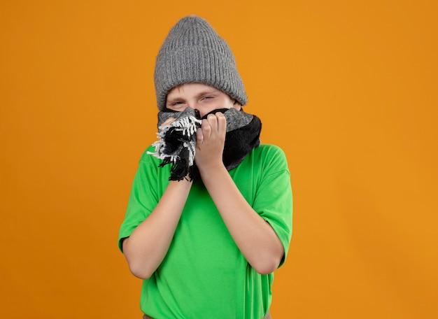 Ragazzino malato che indossa la maglietta verde in sciarpa calda e cappello che copre la bocca con la sciarpa sensazione di malessere in piedi sul muro arancione