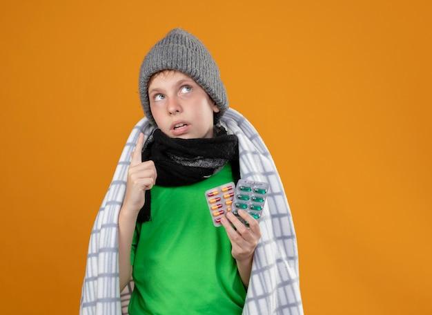 暖かい帽子と毛布に包まれたスカーフを身に着けている病気の少年は、オレンジ色の壁の上に立っている指で上向きに見上げると気分が悪くなる錠剤を保持している熱に苦しんでいます
