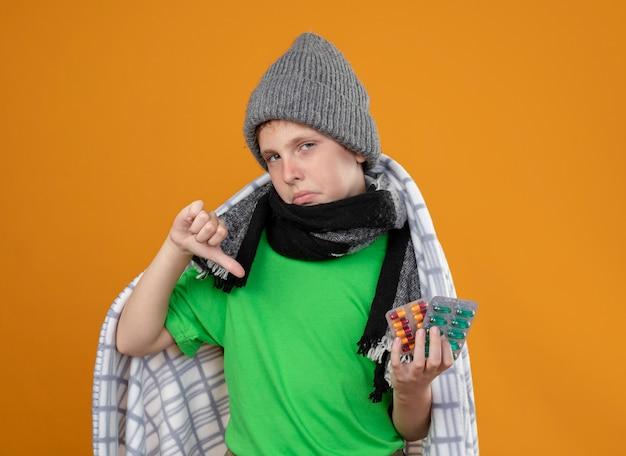 暖かい帽子と毛布に包まれたスカーフを身に着けている病気の少年は、オレンジ色の壁の上に立って親指を下に見せて気分が悪い錠剤を保持している熱に苦しんでいます