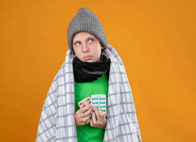 オレンジ色の壁の上に立っている気分が悪いピルを保持している熱に苦しんでいる毛布に包まれた暖かい帽子とスカーフを身に着けている病気の少年
