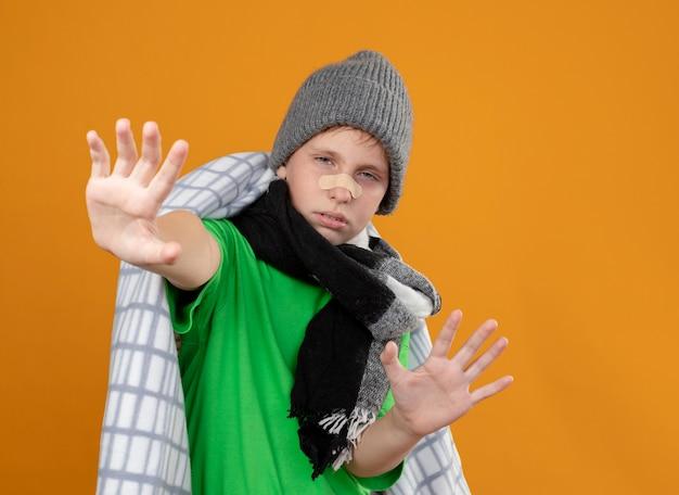 暖かい帽子とスカーフを身に着けている病気の少年は、彼の鼻にパッチが付いた毛布に包まれて不幸で病気に見え、オレンジ色の壁の上に立っている手で防御ジェスチャーをしています