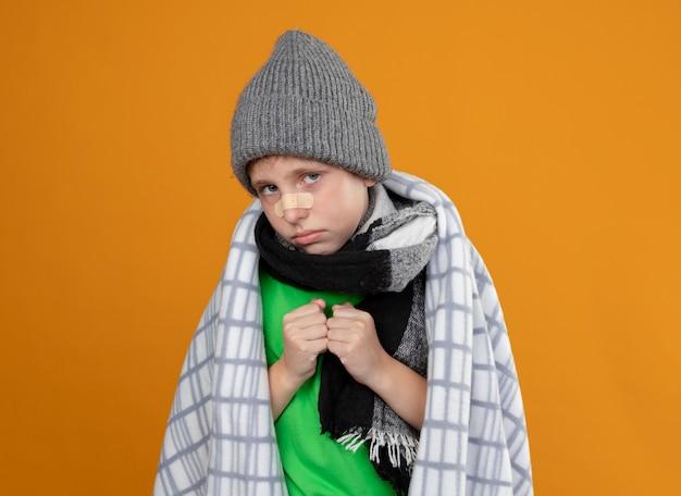 オレンジ色の壁の上に立って不幸で病気に見える彼の鼻にパッチで毛布に包まれた暖かい帽子とスカーフを身に着けている病気の少年
