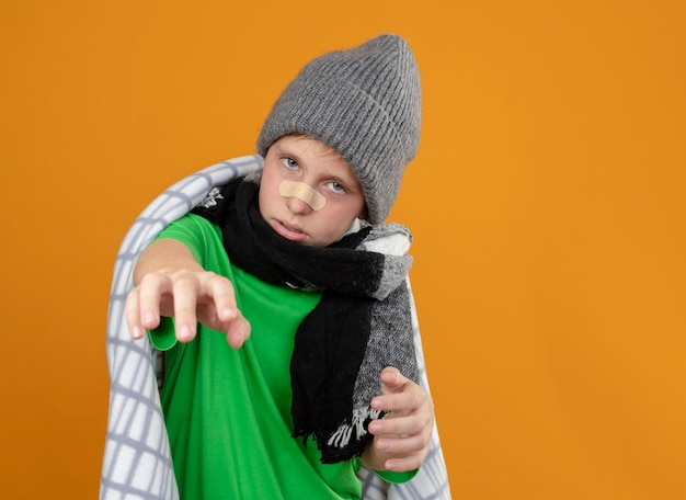 暖かい帽子とスカーフを身に着けている病気の少年は、オレンジ色の壁の上に立って腕を伸ばして見て不幸で病気の鼻にパッチが付いた毛布に包まれています