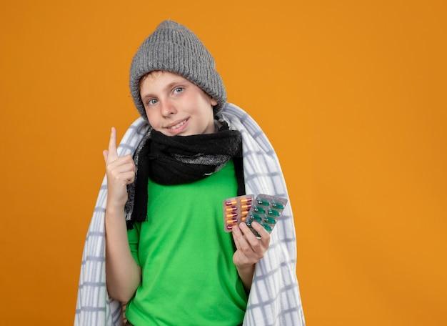 Больной маленький мальчик в теплой шапке и шарфе, завернутый в одеяло, показывает таблетки, чувствует себя лучше, улыбается, показывает указательным пальцем, стоящим над оранжевой стеной