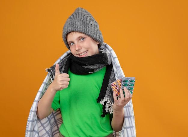 暖かい帽子とスカーフを身に着けている病気の少年が毛布に包まれて丸薬を見せて、オレンジ色の壁の上に立っている親指を見せて笑顔を見せて