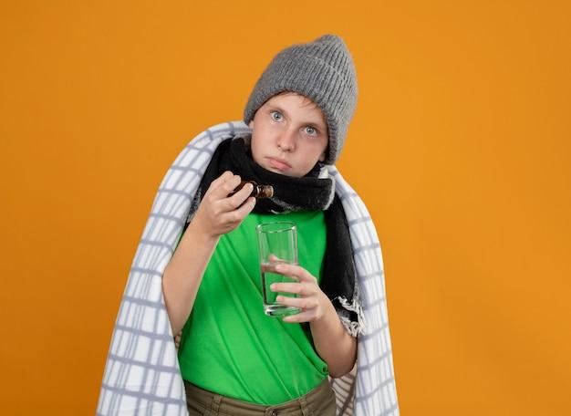 Ragazzino malato che indossa cappello e sciarpa caldi avvolti in gocce gocciolanti di coperta dalla bottiglia di medicina in un bicchiere in piedi sopra la parete arancione