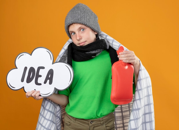 Ill little boy wearing warm hat and scarf wrapped in blanket showing speech bubble sign with word idea and bottle of water to keep warm feeling better smiling