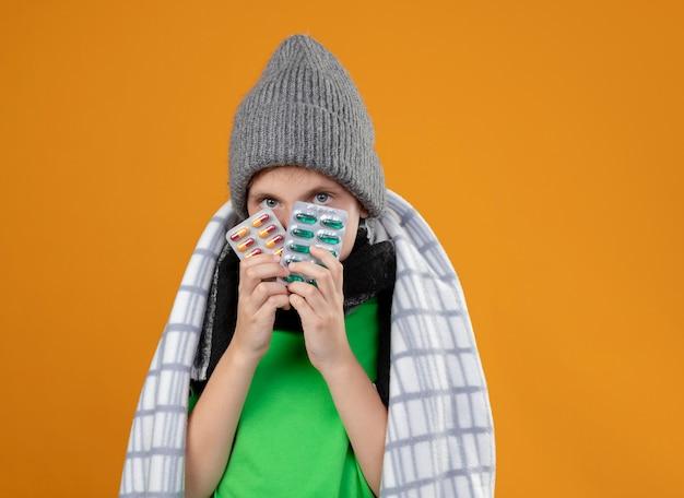 Ragazzino malato che indossa un cappello caldo e sciarpa avvolta in una coperta che soffre di febbre tenendo le pillole sensazione di malessere in piedi sopra la parete arancione