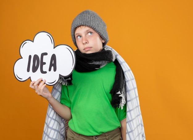 Ill little boy wearing warm hat and scarf wrapped in blanketshowing speech bubble sign with word idea feeling unwell looking up puzzled standing over orange wall