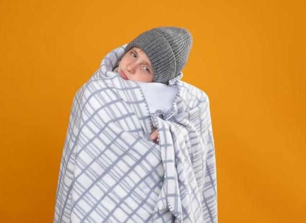 Ragazzino malato che indossa un cappello caldo avvolto in una coperta che soffre di febbre che si sente male oltre il muro arancione