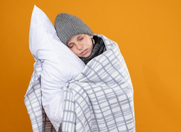 Ragazzino malato che indossa un cappello caldo avvolto in una coperta che soffre di febbre tenendo il cuscino in piedi sopra la parete arancione