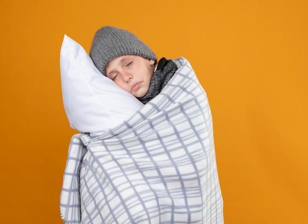 オレンジ色の壁の上に立っている枕を保持している熱に苦しんでいる毛布に包まれた暖かい帽子をかぶっている病気の少年