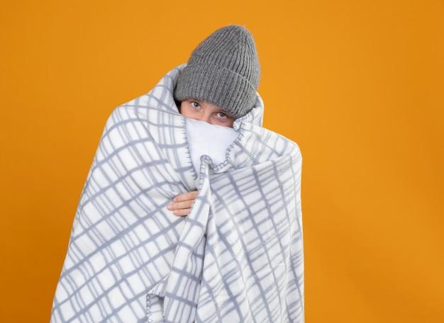 Больной маленький мальчик в теплой шапке, завернутый в одеяло, страдает от лихорадки, стоит у оранжевой стены