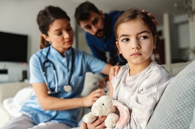 치료와 주사를 받고 아픈 어린 소녀