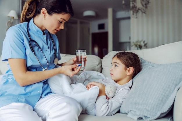 病気の少女が自宅のソファに横になり、看護師からのアドバイスを聞いている