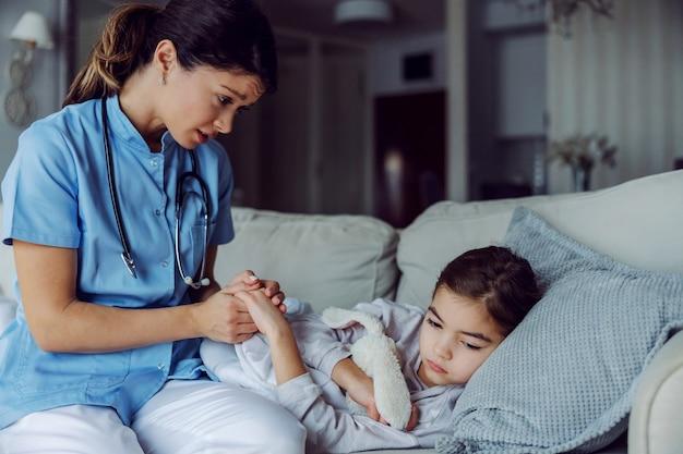 看護師が手を握っている間、自宅のベッドで横になっている病気の少女。病気の少女を慰める看護師。