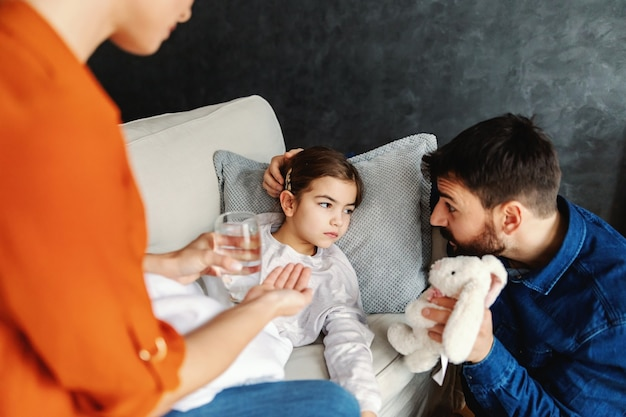 ソファに横になって父親の話を聞いている病気の少女。母は娘にピルと水を与えています。