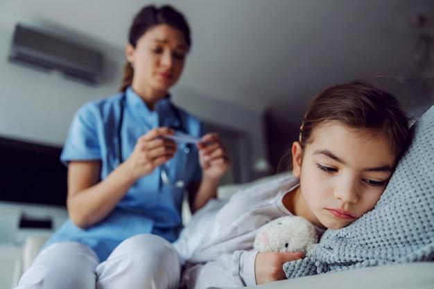 家のベッドに横たわっている病気の少女。ぼやけた背景には、体温計を見ている看護師がいます。
