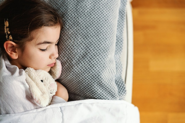 Ill little girl lying on sofa at home, hugging her bunny and sleeping