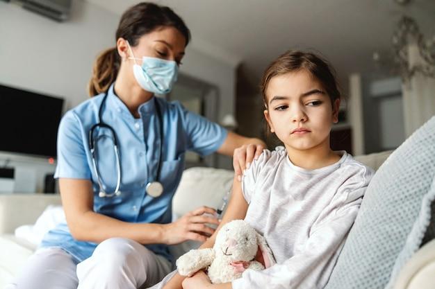Больная маленькая девочка сидит на диване дома и получает инъекцию во время вспышки коронавируса