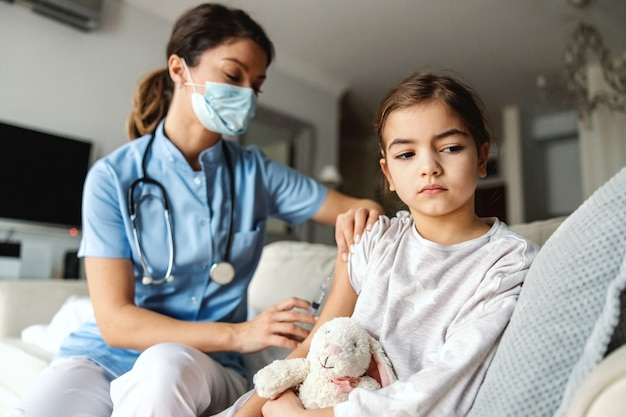 Ill little girl sitting on sofa at home and getting injection during covid outbreak