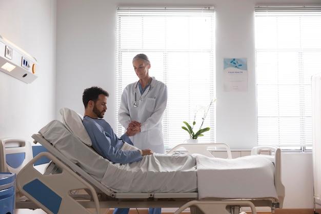 看護師と話しているベッドの病気の男性患者