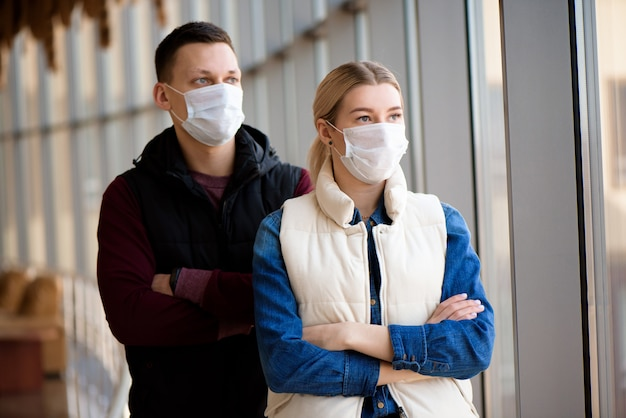 Ill man and woman feeling sick, wearing protective mask against transmissible infectious diseases and as protection against the flu.