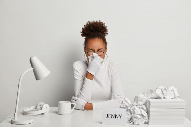 Ill office worker has sneezing and running nose, symptoms of flu