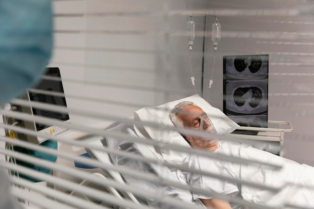Ill old man in a hospital bed with respirator