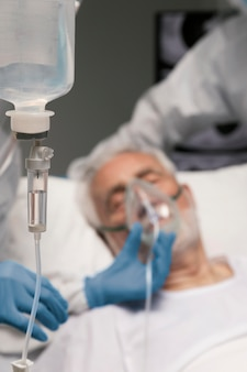 Ill old man in a hospital bed