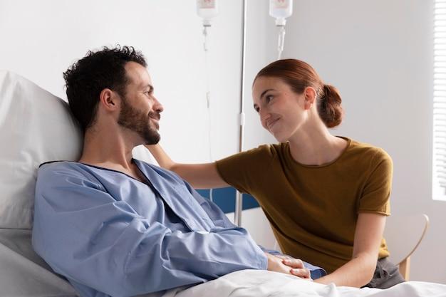 그의 아내와 이야기하는 아픈 환자