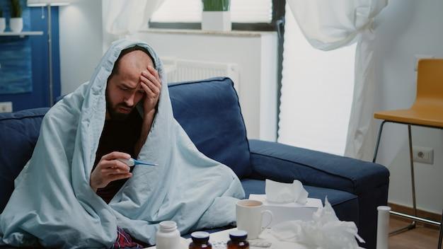 体温計を見て毛布に包まれた病気の人