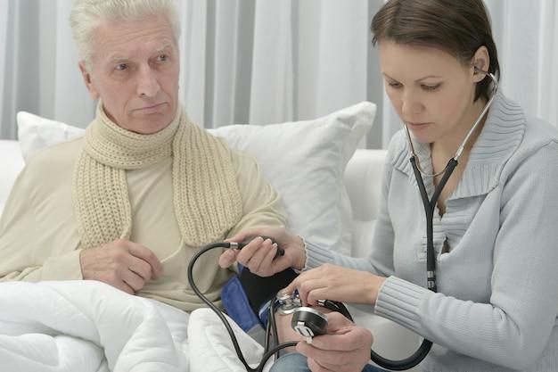 아픈 시니어 남자와 집에서 혈압을 측정하는 돌보는 딸