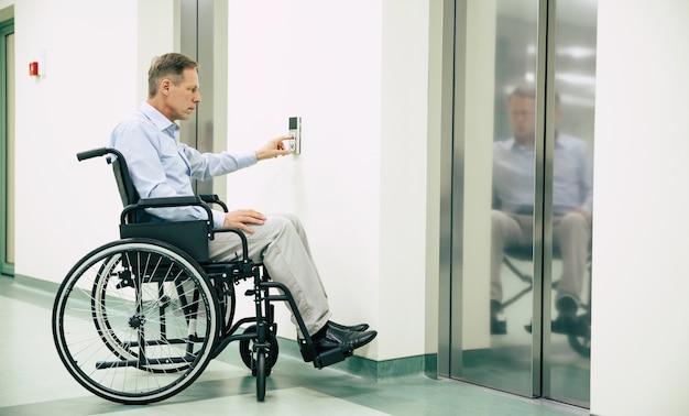 휠체어에 아픈 노인이 병원에서 전화 엘리베이터 버튼을 누르고 있습니다.