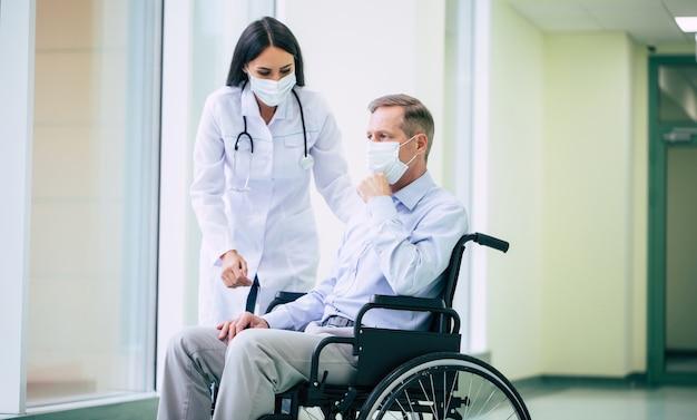 Больной старший мужчина с защитной маской на лице в инвалидной коляске и уверенный врач в медицинской маске во время транспортировки по больнице. Premium Фотографии