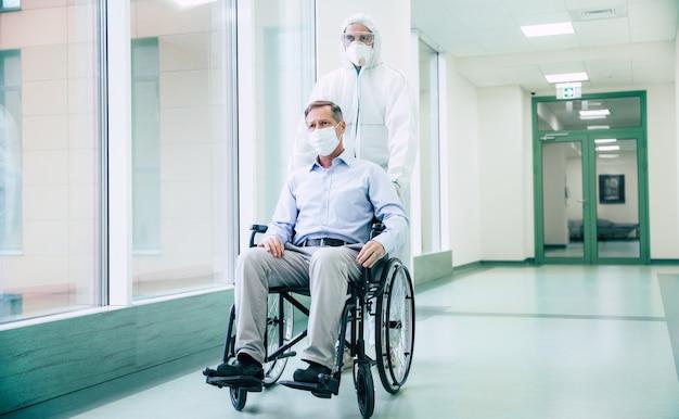 Больной старший мужчина с защитной маской на лице в инвалидной коляске и уверенный врач в медицинской маске во время транспортировки по больнице.