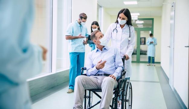 車椅子の顔に保護用防塵マスクを装着し、病院での輸送中に医療用マスクに自信を持っている医師がいる病気の年配の男性。
