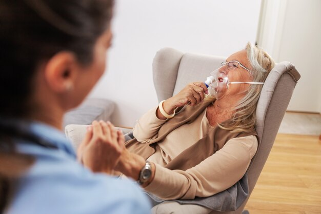 Ill senior woman sitting in chair at home and inhaling oxygen from respirator. nurse sitting next to her, holding her hand and comforting her