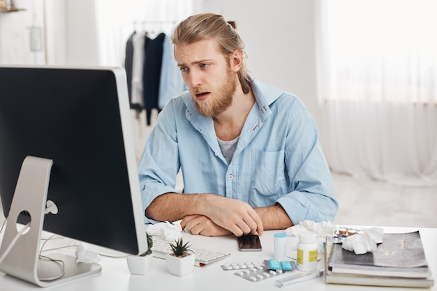 Ill or sick bearded male dressed in blue shirt with tired and suffering face expression, being allergic, having health problems.young man has running nose, sits at workplace with pills and drugs