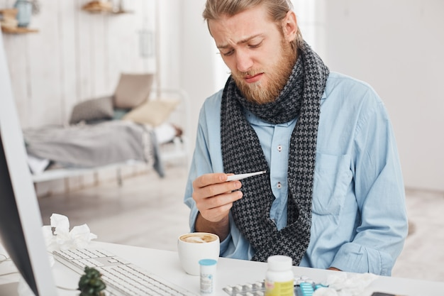 Ill or sick bearded male uses thermometer to measure temperature of his body. fair-haired man desperately looks at thermometer, suffers from bad cold, surrounded by medicine at his workplace.