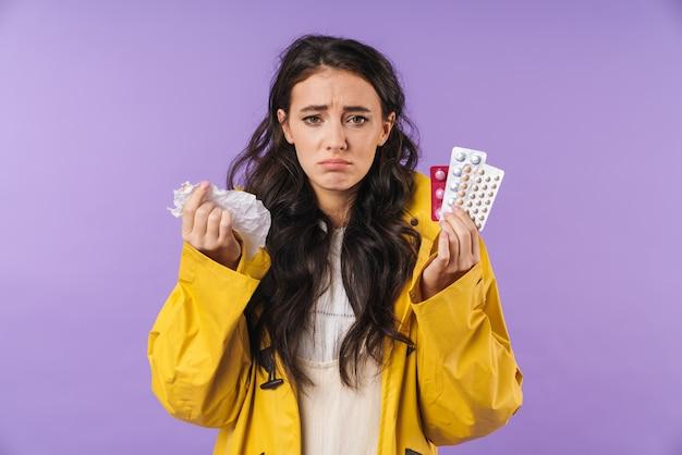 ナプキンと錠剤の薬を保持している紫色の壁の壁に隔離された病気の女性。