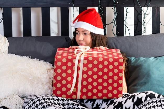 ベッドで休日を待っている赤いサンタ帽子の病気の10代の少女とクリスマスプレゼントに満足