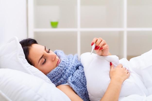 Больная женщина простудилась, подняв температуру и измеряя температуру с помощью термометра. портрет больной девушки с болью в горле, покрытой одеялом, имеющим проблемы со здоровьем. концепция болезни. высокое разрешение