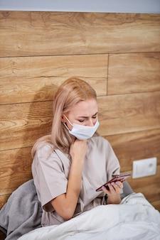 病気の女性は、自宅のベッドにスマートフォンを手に座って風邪をひいた、自宅で咳をするアレルギー症状のある医療用マスクの病気のアレルギー性ヨーロッパ人女性、インフルエンザの概念