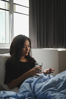 An ill woman is holding a glass of water and consuming a pill at the bed.