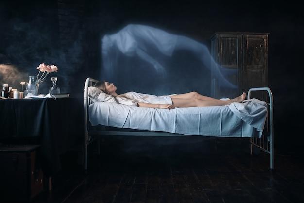 Больная женщина лежит на больничной койке, душа покидает тело