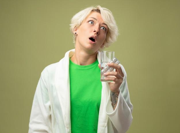 Больная женщина с короткими волосами плохо себя чувствует, держа стакан воды и блистер с таблетками, глядя в сторону, стоя над светлой стеной