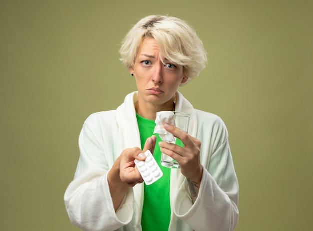 Больная женщина с короткими волосами, которая плохо себя чувствует, держит стакан воды и волдырь с таблетками, недовольная с грустным выражением лица стоит над светлой стеной